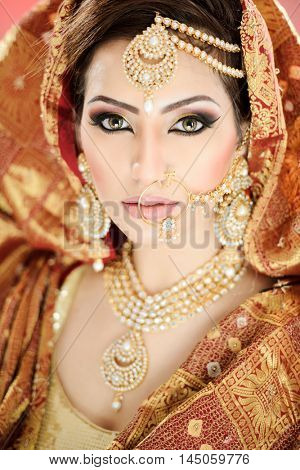 portrait of a pretty indian pakistani girl in traditional bridal costume with heavy makeup and jewelry