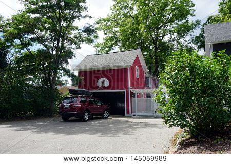 PETOSKEY, MICHIGAN / UNITED STATES - AUGUST 5, 2016: A red GMC Acadia is parked in front of the red garage of a home near downtown Petoskey.