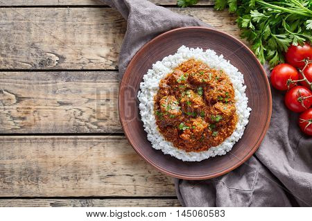 Madras butter Beef spicy traditional Indian masala slow cook lamb meat food with rice and tomatoes in clay plate on vintage wooden table background. Delicious India culture restaurant dish.