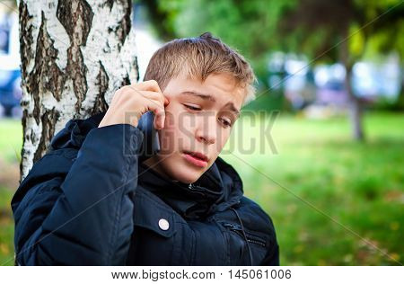 Stressed Teenager with Cellphone in the Park
