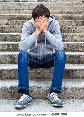 Sad Teenager sit on the City Street