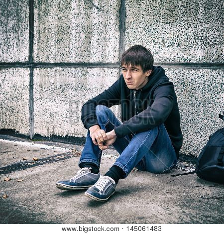 Toned Photo of Sad Teenager sit by the Wall on the Street