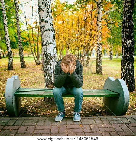Toned Photo of Stressed Teenager sit on the Bench in the Autumn Park