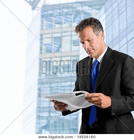 Businessman reading morning news standing against his modern building exterior