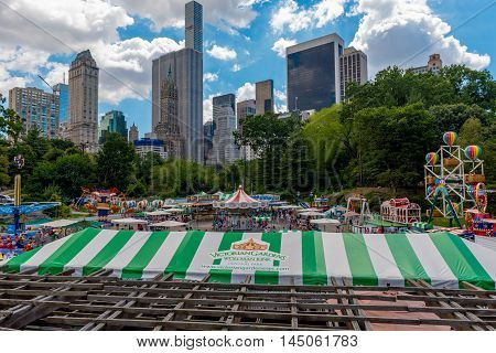 Central Park New York US -- August 31 2016. Victorian Gardens amusement park in Central Park with city skyscrapers in the backgound under a dramatic blue sky and white clounds. Editorial Use Only.