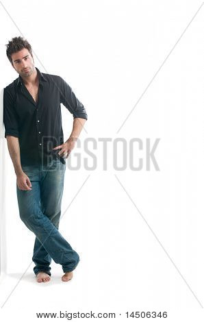 Smiling young latin man leaning against a white wall with copy space for your text isolated on white background
