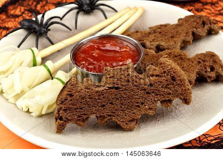 Halloween Party Food With Bat Breads And Cheesy Witch's Broomsticks, Close Up Table Scene