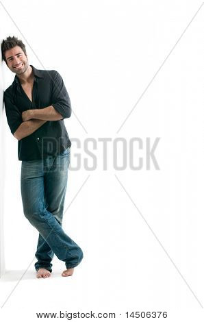 Smiling young latin man standing against a white wall with copy space for your text isolated on white background
