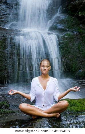 Beautiful young woman doing yoga in lotus position near waterfall