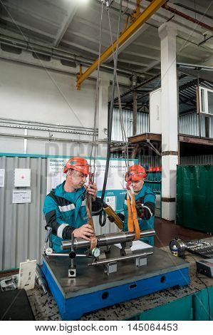 Tobolsk, Russia - July 15. 2016: Sibur company. Polymer plant. Mechanics transfer detail to workbench by crane