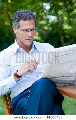 Mature man reading a newspaper outdoor