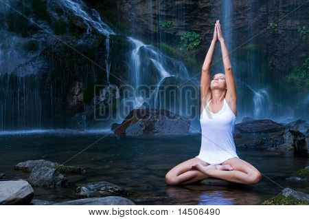 Beautiful young Woman doing Yoga Lotus-Position in einem Wasser-Pool in der Nähe von Wasserfall