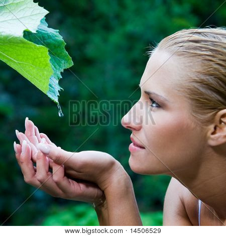 Beautiful young woman take a drop of clear water from a leaf in the nature. Symbol of purity, body care and nature harmony