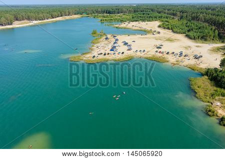 Aerial view onto beach on so-calles Blue Lake and people swim on inflatable mattresses