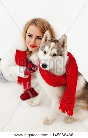 Girl with red scarf sitting with a Siberian Husky in the snow. On the lips of the girl red lipstick. Soft focus.