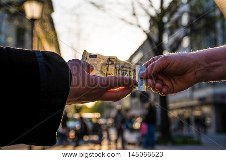 Two Hands Exchanging 5 Euro Note Sunlight