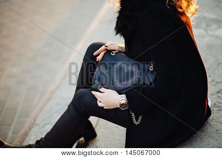 Closeup fashion portrait of young stylish hipster girl posing in the sunset, stylish feminine look, a black coat, party bag, toned colors, soft vintage colors, fashionable object, sitting on the stairs.