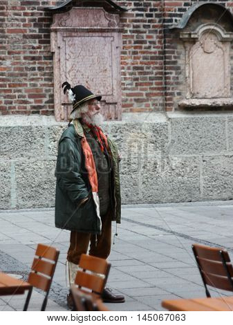 Munich, Germany - November 2011. Man in national dress Tyroleans stands on the street with a hat with a feather