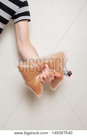 hand holding plastic bag with tap full of apple juice, stucco wall background