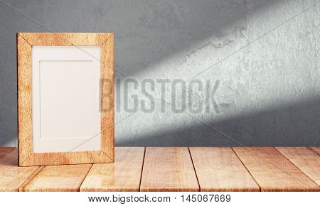 Blank frame on wooden table over gray background. 3d rendering
