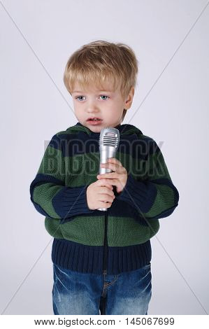 photo of cute little singing boy with mic