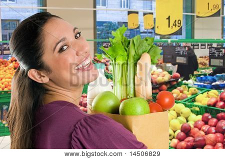 Young woman holding a grocery bag full of fresh and healthy food inside a supermarket