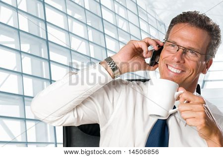Mature businessman taking a break with a cup of coffee in his modern office