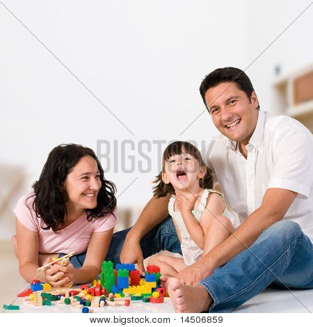 Happy family with parents and daughter playing with colorful blocks inside at home