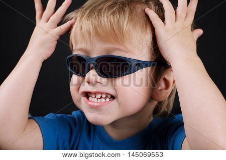 photo of little emotional boy with sunglasses