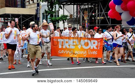 New York City - June 29 2013: Members of The Trevor Project with their orange banner marching in the 2013 Gay Pride Parade on Fifth Avenue