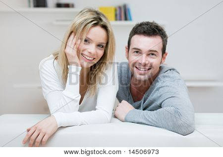 Young happy couple smiling together at camera in their home