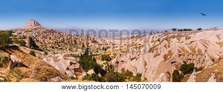 Panorama of the Pigeon valley and view on Uchisar village with a castle and a Turkish flag on top. Cappadocia, Turkey