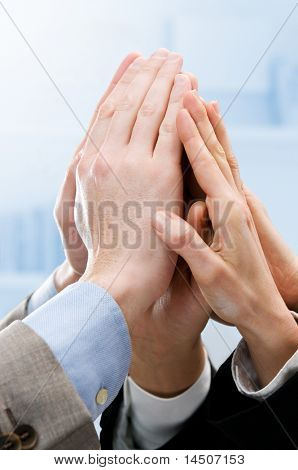 Group of hands raised up for an high five in the office. Symbol of teamwork, victory and success
