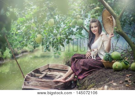 happy mature beautiful asian woman with boat gardener cares for grapefruit in organic farm