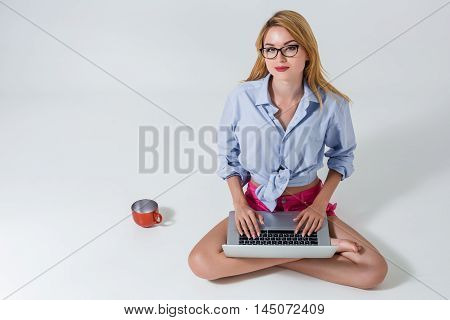 young woman sitting on the floor with crossed legs and using laptop on white background. satisfied, pleased, happy, smiling and looking at the camera