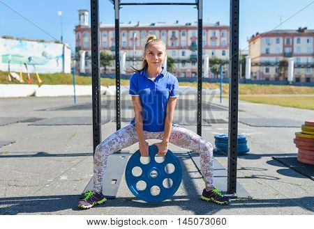 Young beautiful woman squatting with weight outdoors.