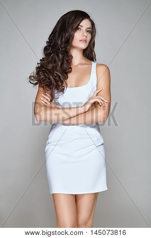 Portrait of attractive woman with curly hair in white short dress on gray background.
