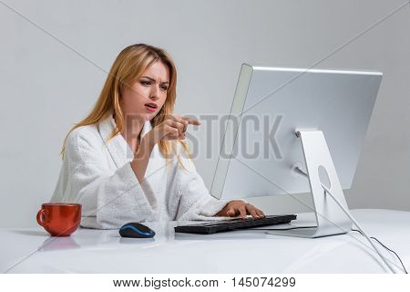 young woman sitting in the table and using computer on gray background. indignation is pointing at the monitor