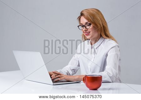 Young businesswoman working at laptop computer. she smiles, prints and looking at monitor