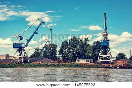 Blue cranes in cargo port translating coal. Industrial scene. Retro photo filter. Danube river.