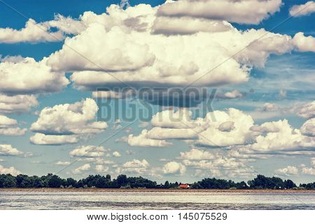 Waterfront with trees and house and blue sky with big clouds. Danube river. Natural scene. Beauty in nature. Retro photo filter. Travelling theme. Summer vacation.