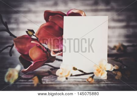 Close Up of Blank Vertical Card with Copy Space Framed by Colorful Spring Blossoms on Rustic Background