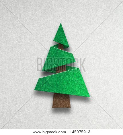 Single modern conical green pine of fir Christmas tree in a stylised textured cutout design with shadow on grey with copy space for your seasonal greeting
