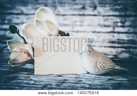 Small White Bird Figurine with Blank Horizontal Card and Blossoms on Rustic Wooden Background