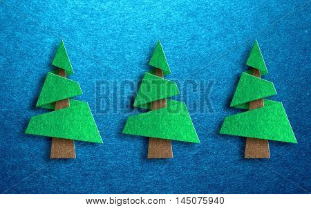 Seasonal greeting card design with three dimensional conical shaped pine trees against a blue textured background