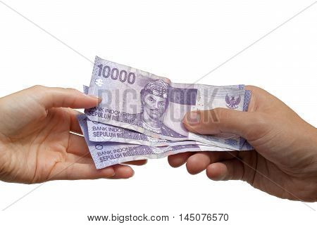 Paying - hand giving Indonesian rupiah banknotes to another hand