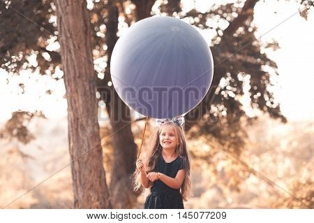 Cute kid girl 4-5 year old holding big balloon outdoors. Smiling child girl. Wearing stylish dark blue dress. Childhood.