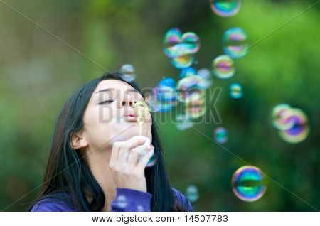 Young beautiful girl blowing bubbles in the nature, symbol of hope and aspirations