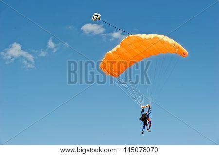 Kharkiv Ukraine - August 20 2016: Skydiver flying on orange parachute at the airfield Korotych Kharkov region Ukraine on August 20 2016