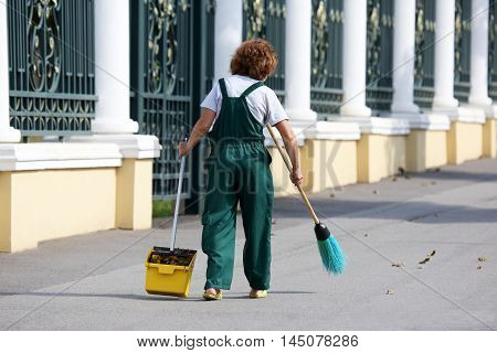 janitor woman cleans the sidewalk of the city from fallen leaves